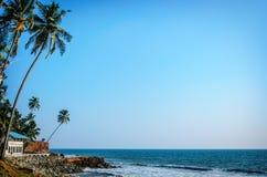 Tropical Indian village  in Varkala, Kerala, India. Tropical Indian village with coconut palm trees near the road and blue ocean in Varkala, Kerala, India Royalty Free Stock Images