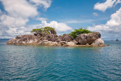 Tropical island. Tiny island in Southeast Asia with four visiting boats Stock Photography