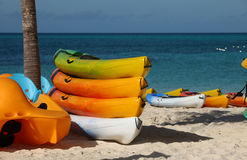 Tropical Island Activities. White sand beach with Sea kayaks of various colors Stock Photo