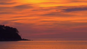 Tropical Island. A beautiful silhouette of a tropical island against an orange golden sky right after sunset. You see a person paddling a kayak in the distance stock footage