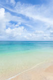 Tropical island beach and clear blue coral water Stock Images