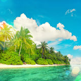 Tropical island beach landscape with palm trees. Light leaks. Landscape of tropical island beach with palm trees and cloudy blue sky. Retro style toned picture Royalty Free Stock Image