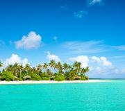Tropical island beach with palm trees and cloudy blue sky royalty free stock photo