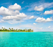 Tropical island beach with palm trees and cloudy blue sky Royalty Free Stock Photography