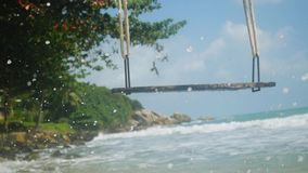 Tropical Island Beach with swing. Splashing waves in the Sea in slow motion. 1920x1080, hd. Tropical Island Beach and Swing. Splashing waves in the Sea in slow stock footage