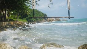 Tropical island beach with swing. Splashing waves in the sea in slow motion. Paradise at Koh Samui. 1920x1080. Tropical island beach and swing. Splashing waves stock video footage