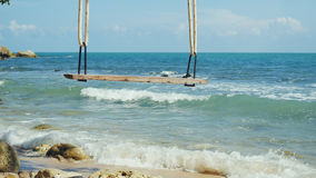 Tropical Island Beach and Tree Swing. Splashing waves in the Sea at stones on beautiful background on the blue sky. Stock Photo