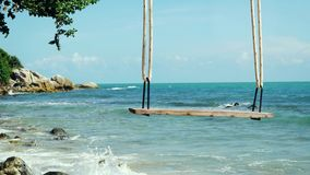 Tropical Island Beach and Tree Swing. Splashing waves in the Sea at stones on beautiful background on the blue sky. Paradise at Koh Samui, Thailand stock video