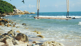 Tropical Island Beach and Tree Swing. Splashing waves in the Sea at stones on beautiful background on the blue sky Stock Photos