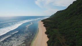 Tropical Island Coastline Aerial. Tropical island coastline with cliffs, green mountain and ocean waves stock footage