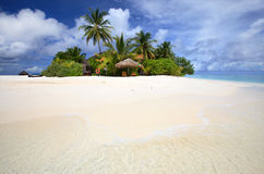 Tropical island, coulpe paradise. Beautiful tropical island vacation paradise with white sand, tall palm trees, fluffy white clouds, a dark blue sky and Stock Image