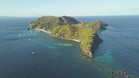 Tropical island covered tropical forest in blue sea aerial landscape. Amazing view from drone ships and boats floating stock video footage