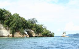 Tropical island with double arch. Limestone island overgrown by bushes and trees with arch in arch in Lembeh Strait, North Sulawesi, Indonesia Stock Image