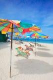 Tropical island getaway. Idyllic tropical island getaway with sunbeds on white sandy beach Royalty Free Stock Image