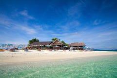 Tropical island getaway. Idyllic tropical island getaway with sunbeds on white sandy beach Royalty Free Stock Photography
