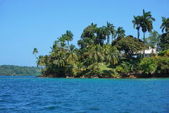 Tropical island with an house viewed from the sea Stock Image