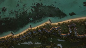 Tropical island with houses on the coast, aerial view. Aerial view of green island landscape with row of houses along the ocean coast. Le Morne Brabant peninsula stock video footage
