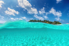 Tropical island on Indian Ocean, Maldives. Half underwater shot Stock Photos