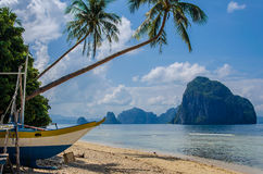 Tropical island landscape, El, Nido, Palawan, Philippines, Southeast Asia. An boat under Palms on Tropical island, bis Rock island on background, cloudy sky El Stock Image