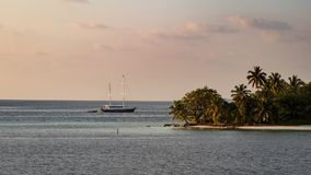 Tropical island and sailing yacht at sunset royalty free stock image