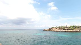 Tropical island Nusa Lembongan in Indonesia. Sunny day, blue ocean, waves, rocks. stock footage