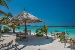 Tropical island with palm trees and amazing vibrant beach in Maldives. Parasol in sea tropical Maldives romantic atoll island. Paradise luxury resort about Stock Photography