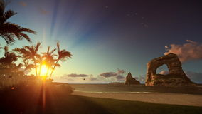Tropical island with palm trees and rocks in ocean at sunrise, tilt stock video footage