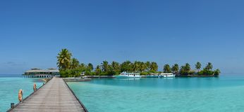 Tropical island panorama at the Maldives with boats and docks. Beautiful tropical island panorama at the Maldives with boats and docks at the end of wooden Stock Photos