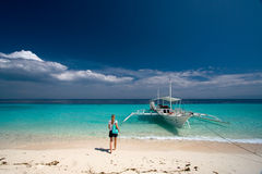 Tropical Island paradise. Remote tropical island paradise surrounded by blue water lagoon with a young woman walking towards a white boat Royalty Free Stock Photo