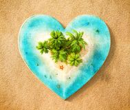 Tropical island. Piece of tropical island with water and palms on a beach in cross section in shape of heart.  Unusual travel illustration. Top view Stock Photography