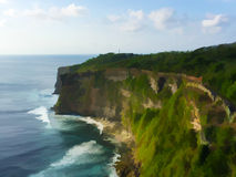 Tropical island`s cliff coast and oceanic wave. Uluwatu temple of Bali, Indonesia Royalty Free Stock Photos