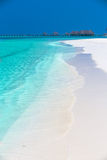 Tropical island with sandy beach, palm trees, overwater bungalow Stock Photos