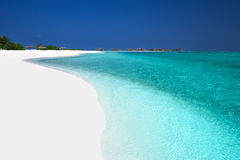 Tropical island with sandy beach, palm trees, overwater bungalow Royalty Free Stock Images