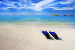 Tropical island with sandy beach and snorkeling equipment Royalty Free Stock Photo