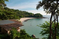 Tropical island with sandy shoreline and resort. Panoramic view of green coastline washed with ocean water in sunlight, Thailand royalty free stock image