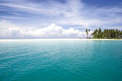 Tropical Island and Sea. Image of a remote Malaysian tropical island with deep blue skies, crystal clear waters, atap huts and coconut trees Stock Photography