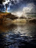 Tropical Island Storm. Large wave crashing into rocky coast during storm, lightning striking lighthouse in background Stock Image