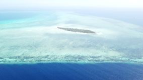 Aerial View of Remote Island in Wakatobi, Indonesia. A tropical island is surrounded by a huge coral reef in Wakatobi National Park, Indonesia. This region is stock video