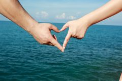 Beautiful young couple is making heart with the fingers stock photography