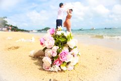 Wedding bouquet in front of young couple background stock photo