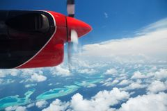 Tropical islands, view from hydroplane. Clouds in blue sky, flight under islands in the ocean royalty free stock photo