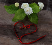 Tropical jasmine flower and Bell red Bow on wood. Jasmine flowers stock image