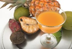 Tropical juice and exotic fruits. Glass of tropical juice on platter with fruits stock image