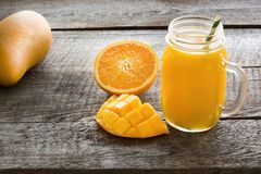 Tropical juice of mango, orange, banans fruit in jar with straw on wooden board. Stock Photo