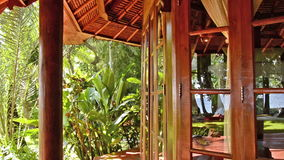 Tropical jungle behind the windows of a bungalow - Bali. Waving in wind stock video