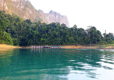 Tropical lakeside hut and wooden boat in ratchaprapa Dam,Khao Sok Royalty Free Stock Image