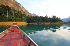 Tropical lakeside hut and wooden boat in ratchaprapa Dam Stock Images