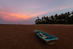 Tropical landscape with boat on the dry beach,with the background is the sunset and mountain, sky at Chumphon,Thailand