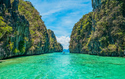 Tropical landscape with cristal clear water. Tropical landscape - cristal clear water, rock islands, lonely boat Stock Image