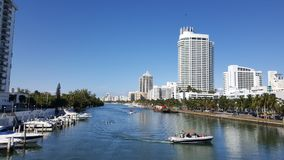 Tropical landscape of Miami coast in a sunny day. Travel and tourism in United States, nature and ocean, blue water and waves, blue sky, buildings in a shoreline stock image